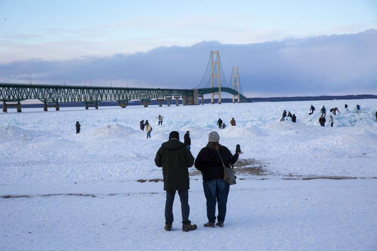 Visitors climb the ice piles near the Mackinac Bridge Friday, Feb. 19, 2021 in Mackinaw City. (Doug Julian/for the Daily News)