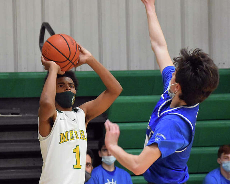 Metro-East Lutheran's Zion Tucker, left, drills one of his four 3-pointers on Monday against Marquette in Edwardsville. Photo: Matt Kamp|The Intelligencer