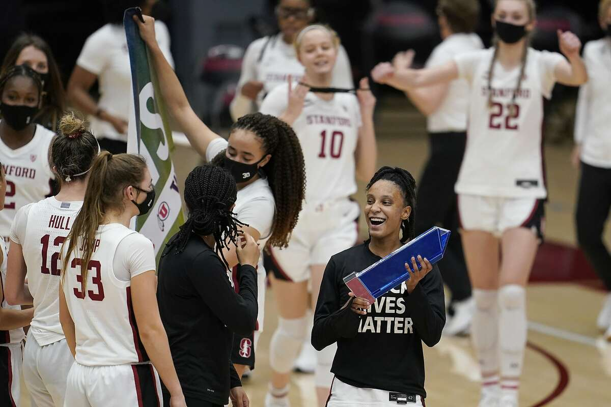 Stanford guard Kiana Williams, bottom right, celebrates with teammates after Stanford defeated Arizona in an NCAA college basketball game in Stanford, Calif., Monday, Feb. 22, 2021.