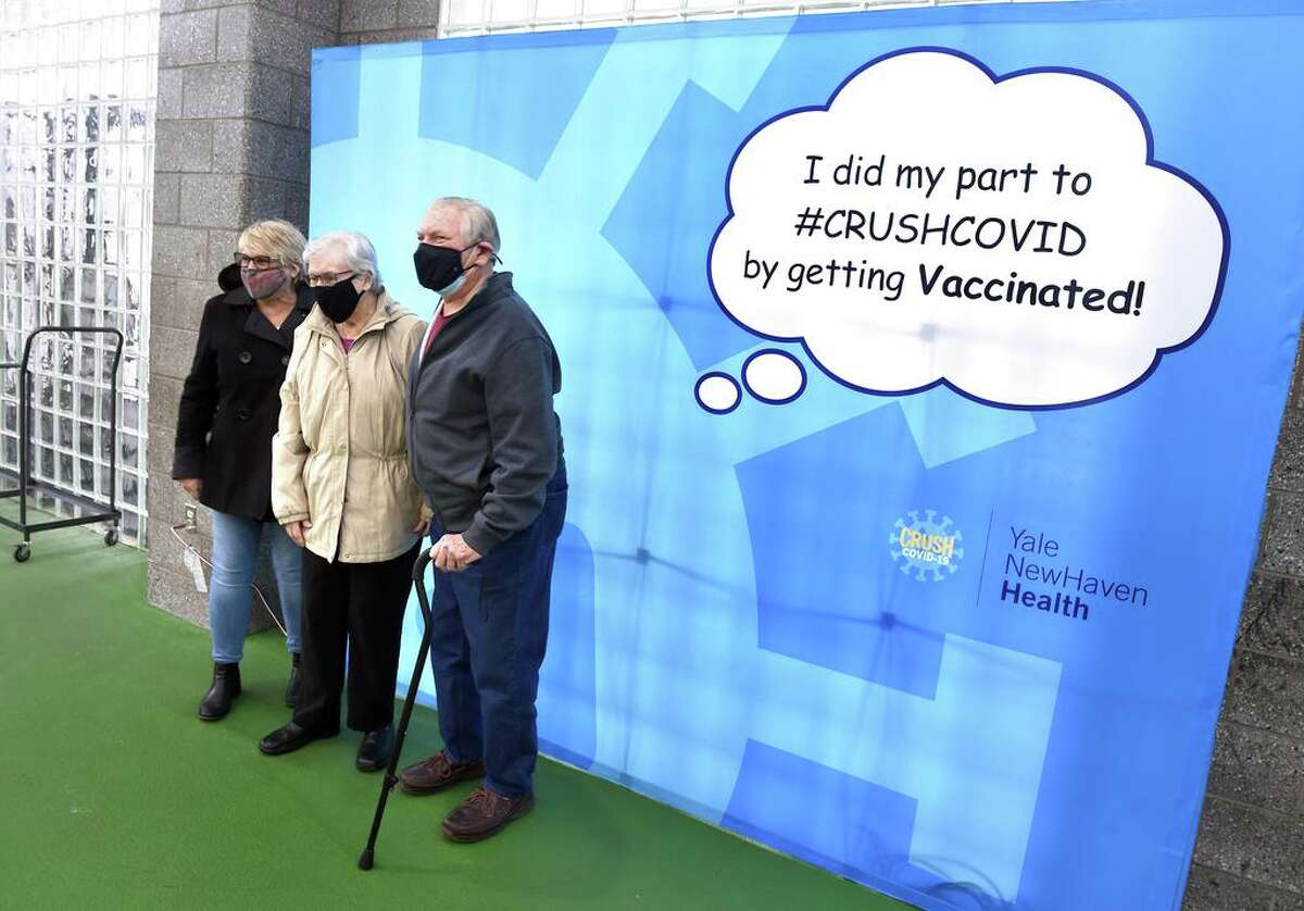 Cathy Cast (center) and her husband, Harry (right), of Branford pose for a photograph with their daughter, Ellen Kemble, after getting a COVID-19 injection at a vaccine clinic at the Floyd Little Athletic Center in New Haven on February 5, 2021.