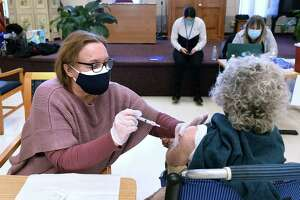 Volunteer retired nurse Maggie Nuzzelillo (left), retired US Army nurse, gives a shot of the Moderna COVID-19 vaccine to Mary Connelly, 93, of Clinton at the East Haven Senior Center on January 29, 2021.