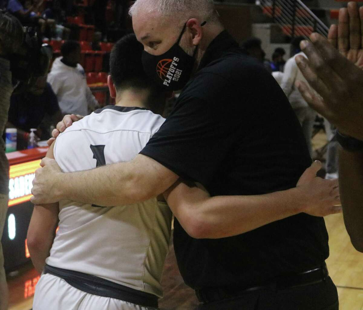 Pasadena head coach Jon Pillow embraces point guard Kanye Ortiz after the surprising Eagles took down their 21-6A adversaries 47-43 Monday night.