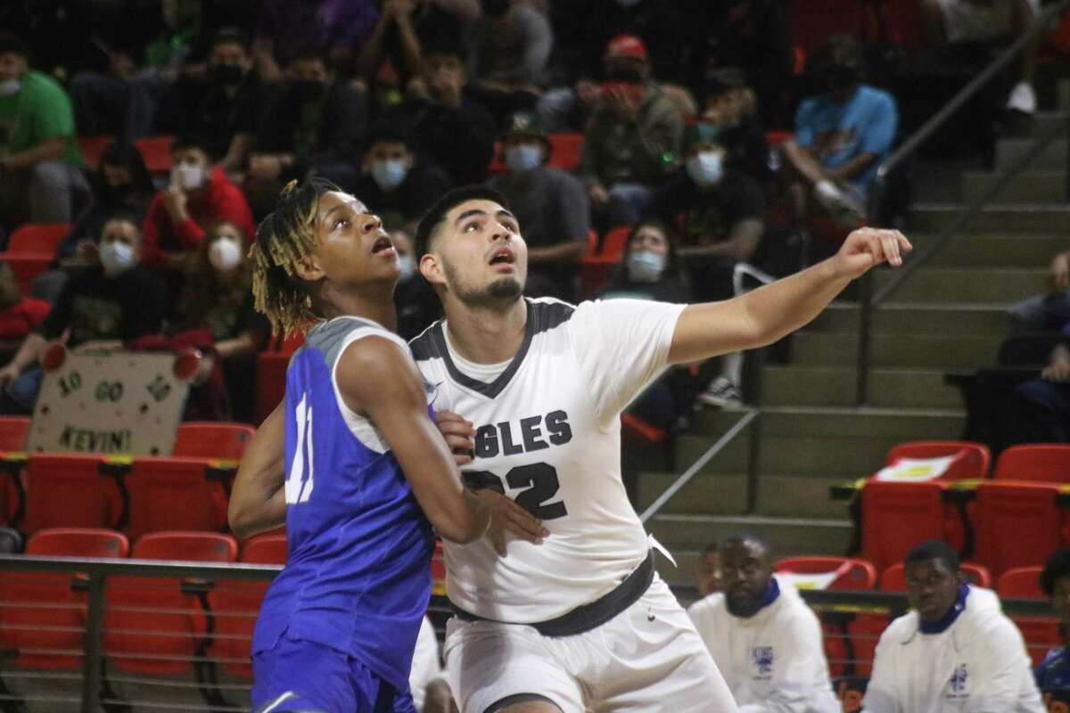 Pasadena's Nelson Herrera and C.E. King's Jayvone Burton await the outcome of a free-throw attempt Monday night,