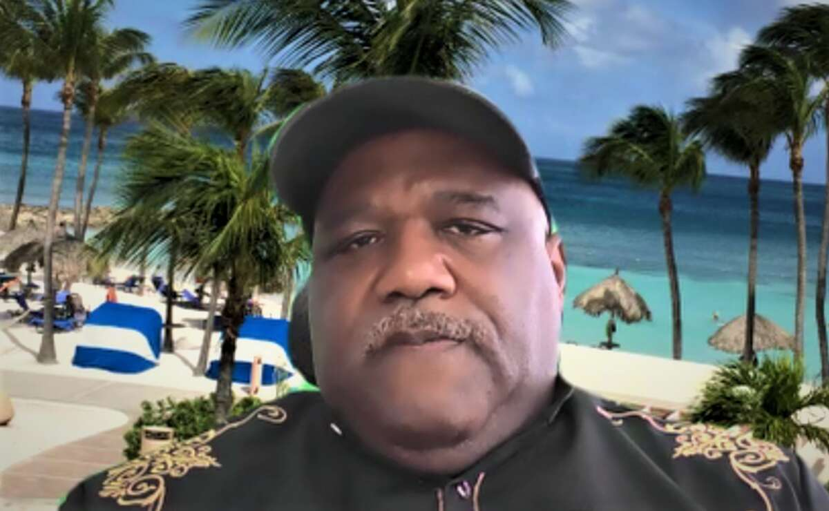 Amos Smith, CEO of the Community Action Agency of New Haven, at an online forum on COVID-19 vaccine access, with a tropical vacation backdrop.