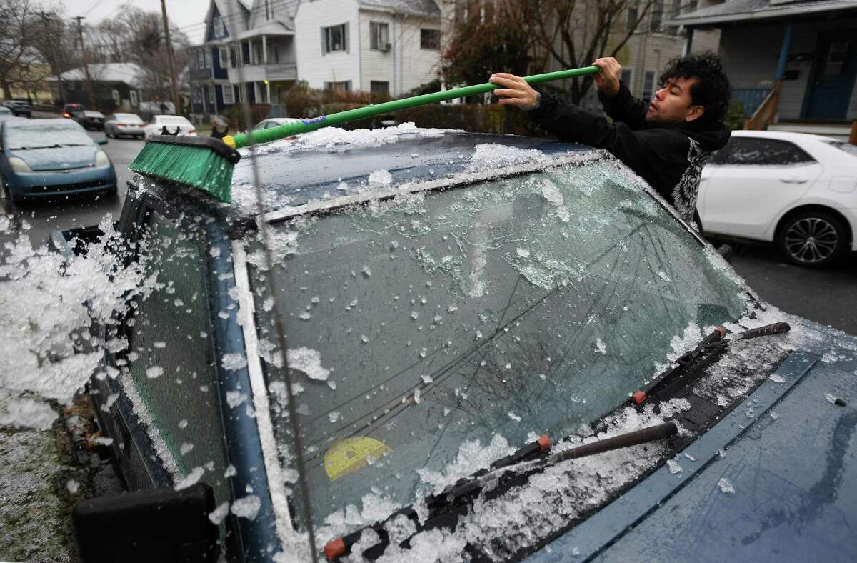 A file photo of a resident clearing ice and snow from his vehicle as he heads to work from his home on Midland Street in the Black Rock section of Bridgeport, Conn., taken on Tuesday, December 17, 2019.