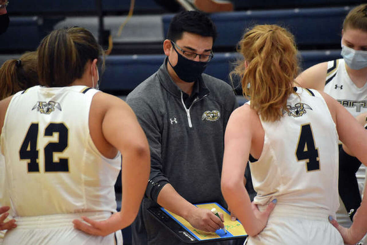 Father McGivney coach Jeff Oller, center, talks to his team during a timeout against Granite City on Saturday.