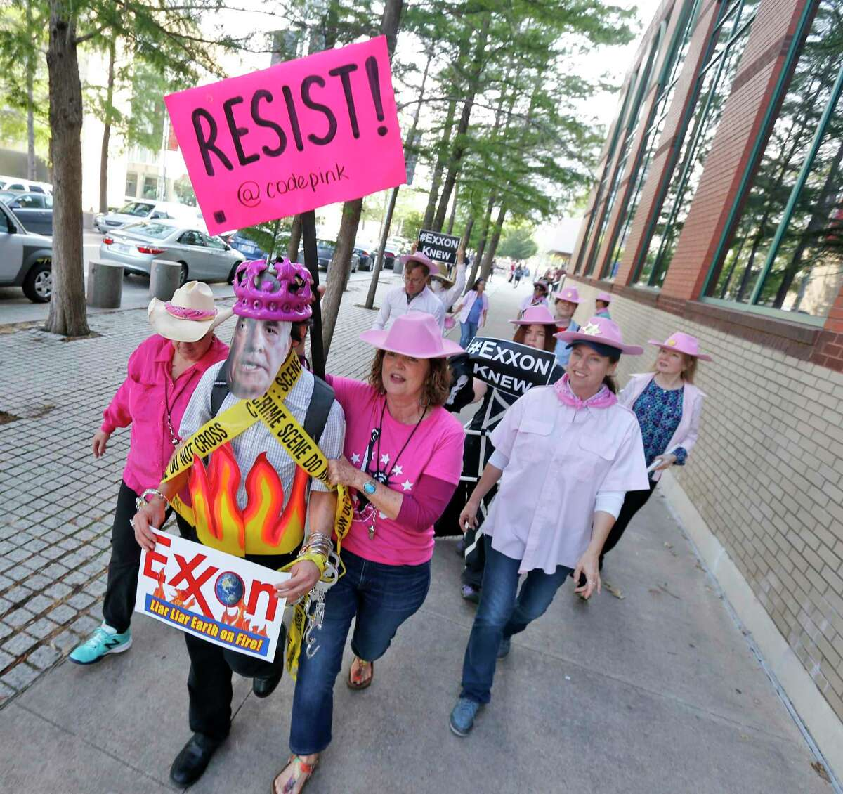 Members of Code Pink, led by Danna Miller Pyke, front with sign, picket and stage a mock arrest of Rex Tillerson, worn by Ernest Jones, as protesters gather outside of the Exxon shareholders meeting across the street from the Morton H. Meyerson Symphony Center in Dallas.