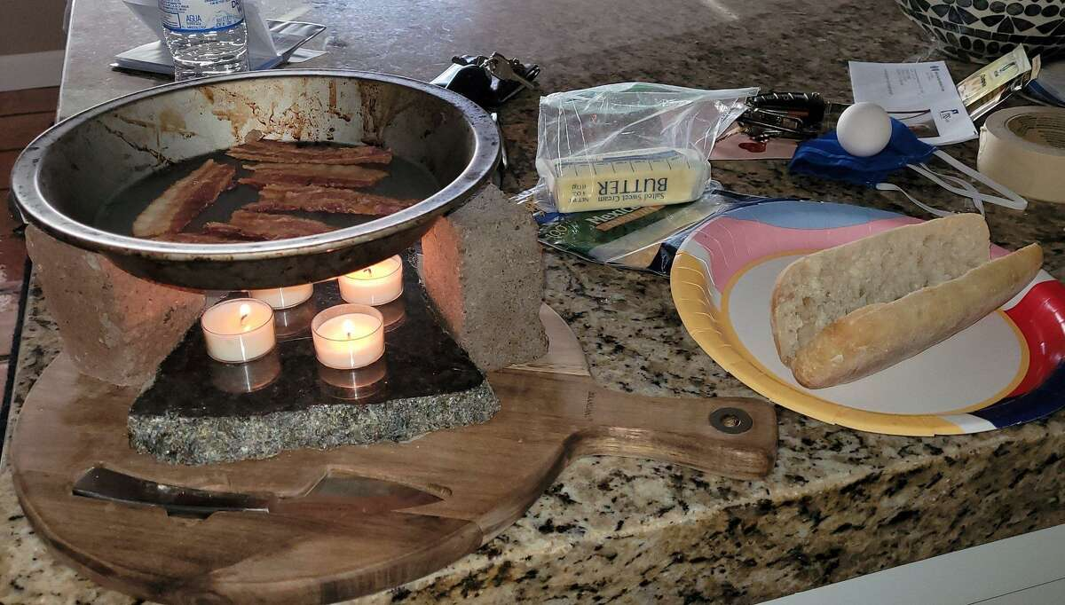 """The tea light """"stove"""" Austin actor Ed Gomez set up in desperation to cook bacon and eggs."""