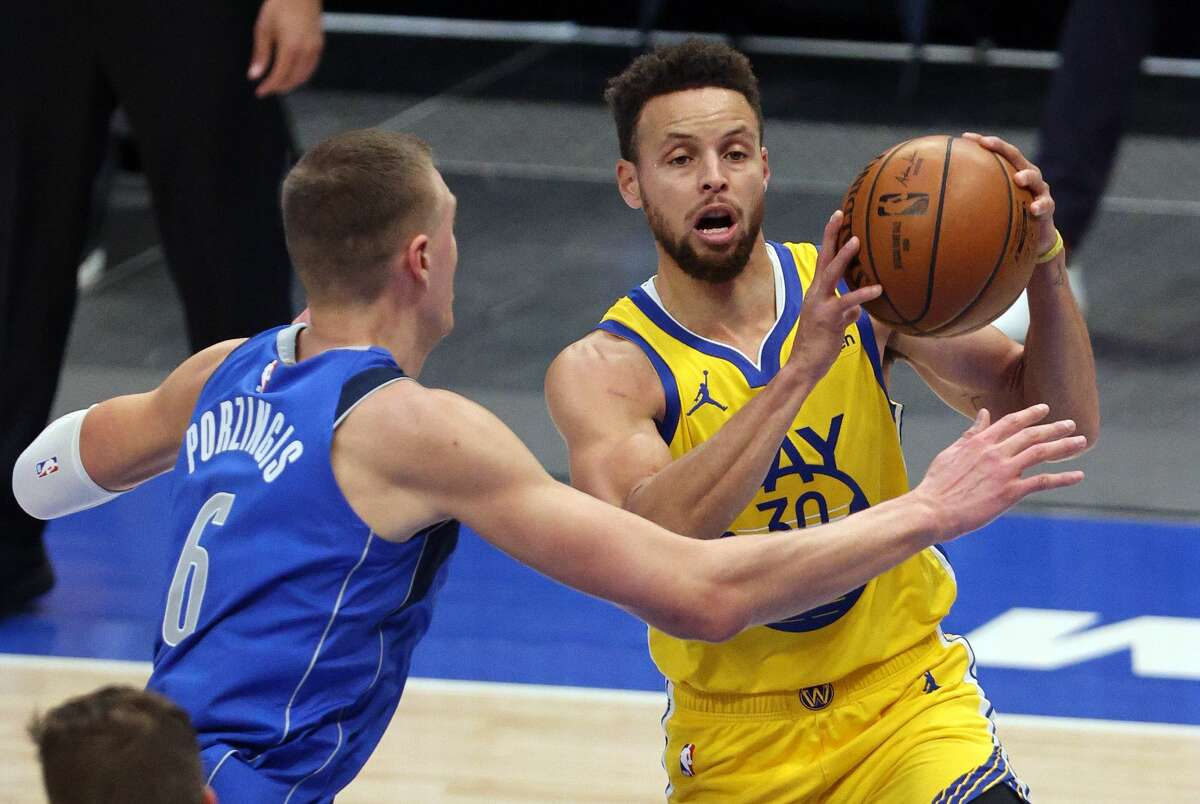 Stephen Curry of the Golden State Warriors takes a shot against Kristaps Porzingis of the Dallas Mavericks on Feb. 4, 2021.