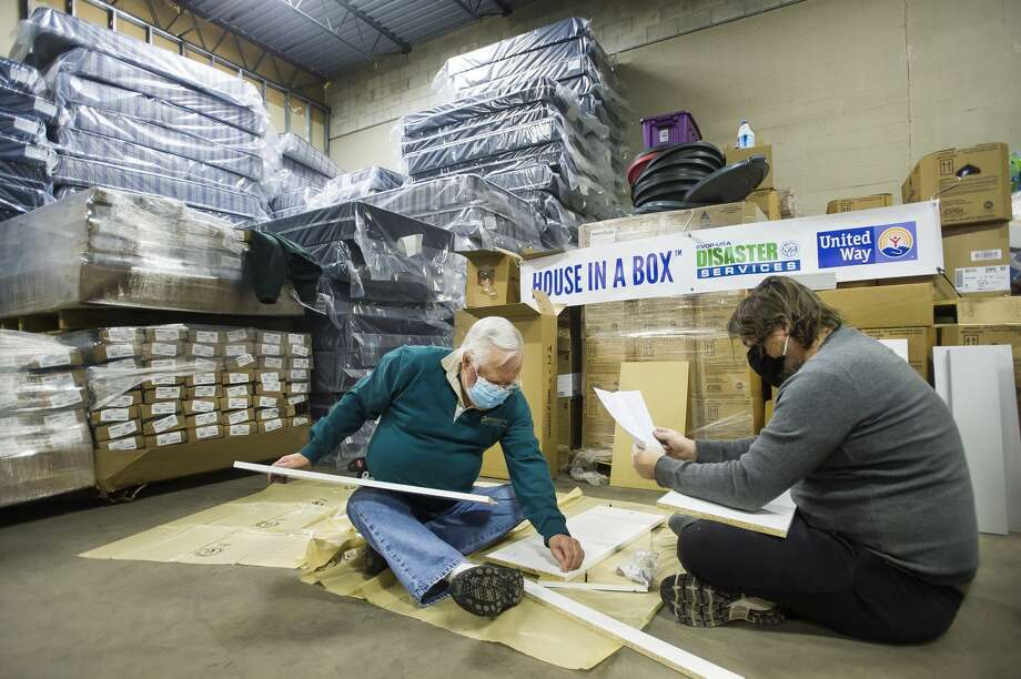 "Volunteers Colin Buell, left, and Parker Buell, right, begin assembling one of 50 ""House in a Box"" kits containing brand new household necessities (couch, bed linens, dinette, dishes, etc.) to distribute to flood survivors Tuesday, Feb. 23, 2021 at the United Way of Midland County warehouse. The project is a collaborative effort between Long Term Disaster Recovery/United Way of Midland County and the Disaster Services Corporation of the Society of St. Vincent de Paul. (Katy Kildee/kkildee@mdn.net) Photo: (Katy Kildee/kkildee@mdn.net)"