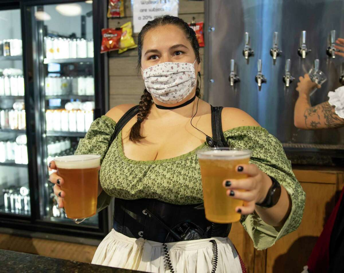 Rissa Kalince brings beer to customers at the bar during Oktoberfest at B-52 in Conroe, Oct. 3, 2020. B-52 will be the first stop on a new Texas Brewery Tour launching from Margaritaville.