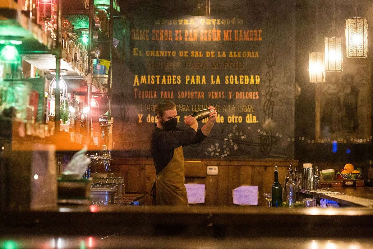 Bartender Robin Hansen mixes cocktails at Padrecitos in San Francisco. The city's restaurants will be able to expand the number of people allowed to dine inside when San Francisco advances to the yellow tier of California's reopening blueprint.