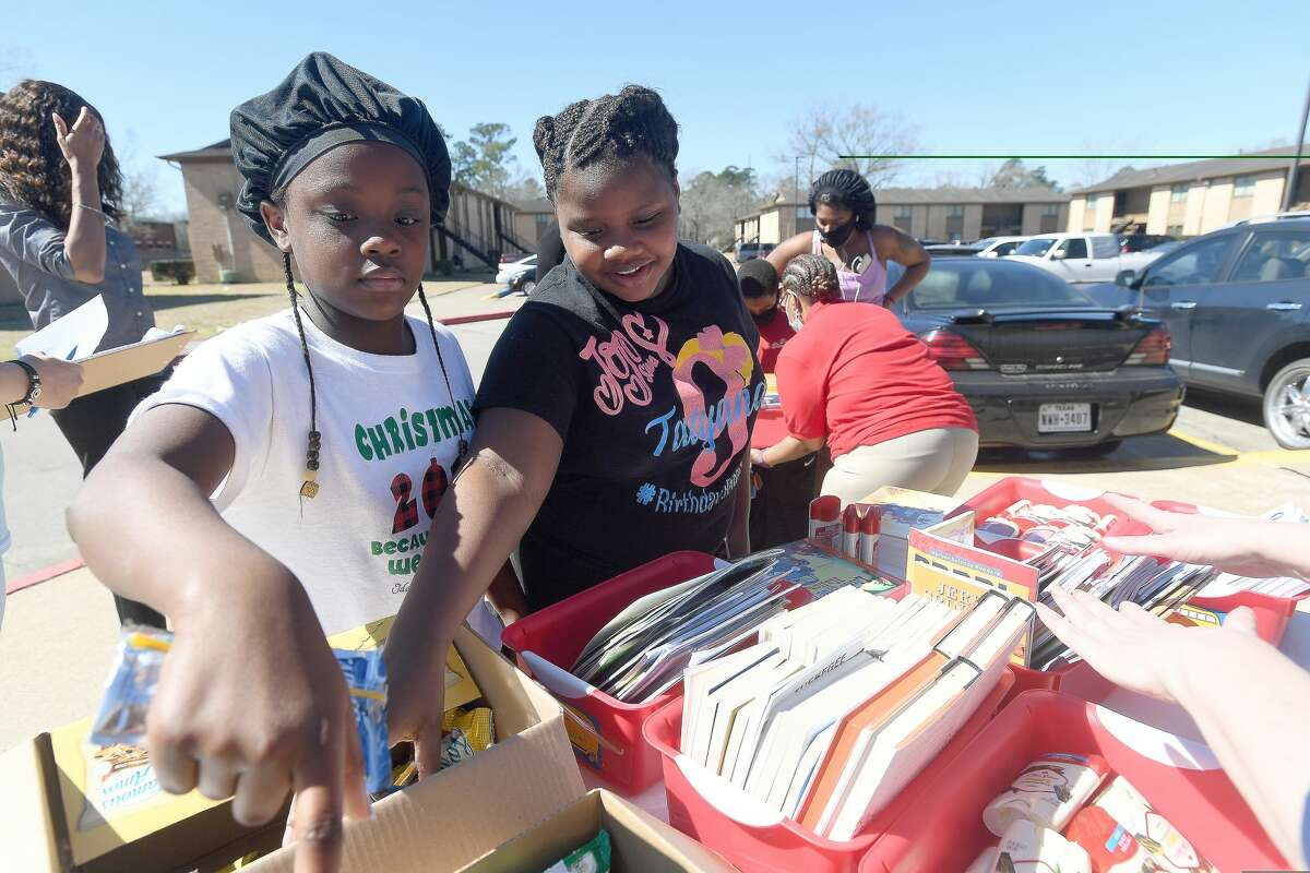 From left, Darion Johnson and Tatyana Charles select snacks after picking out their books during the Beaumont ISD Parent Involvement Committee's caravan Tuesday. Committee members and BISD staff joined in the event to bring books, snacks and toiletries to area students during this week's virtual learning. Photo made Tuesday, February 23, 2021 Kim Brent/The Enterprise