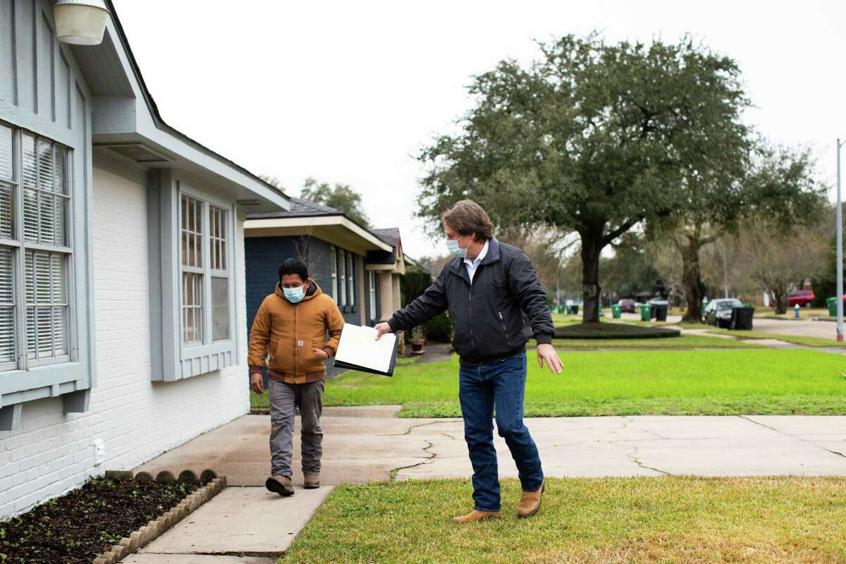 Landscaping business owner Wilber Mendez, left, and real estate agent Charles Goforth, right, discuss changing the flower bed of a home that will go on sale in Westbury, Thursday, Feb. 11, 2021.