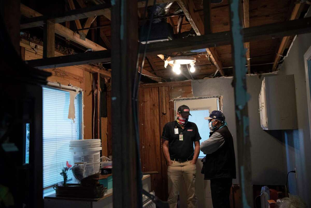 Plumber Troy Watts, left, discusses the damage in Willie Hunt's house from water pipes bursting during last week's frigid storm.