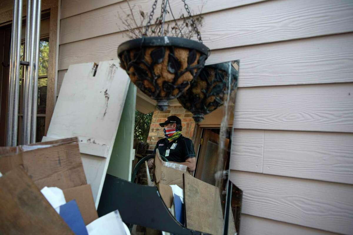 Plumber Troy Watts is seen reflected in a mirror and surrounded by the debris of a Houston home that suffered extensive flooding last week.