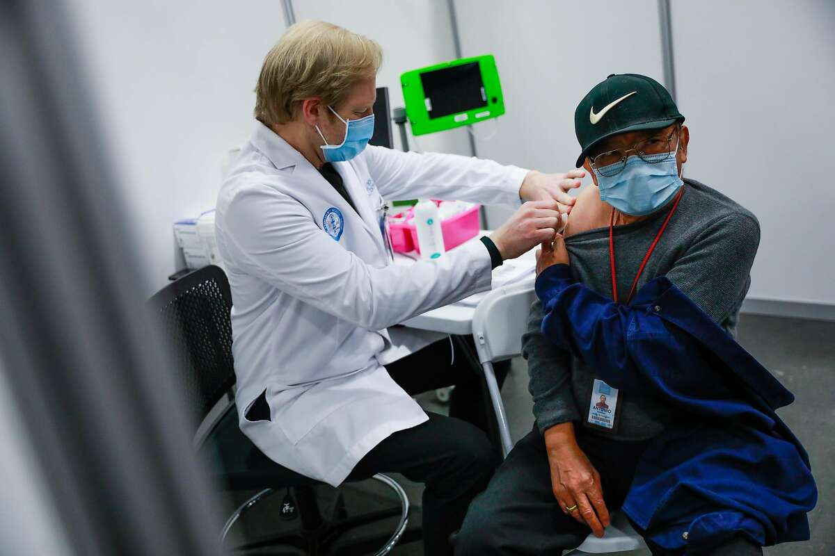 Antonio Rabanal, 73 (right) gets vaccinated at the Moscone Center vaccination site by RN Scott Keech (left) in San Francisco, California. The CDC warns of national rise in virus cases, but Bay Area is still dropping and counties are reopening.