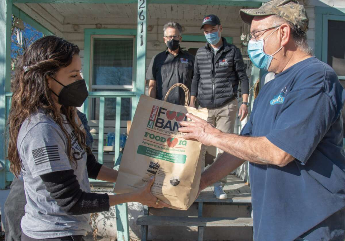 Eva handing food to Frank Campos, a West Side resident who received a delivery on Monday, according to the San Antonio Express-News.