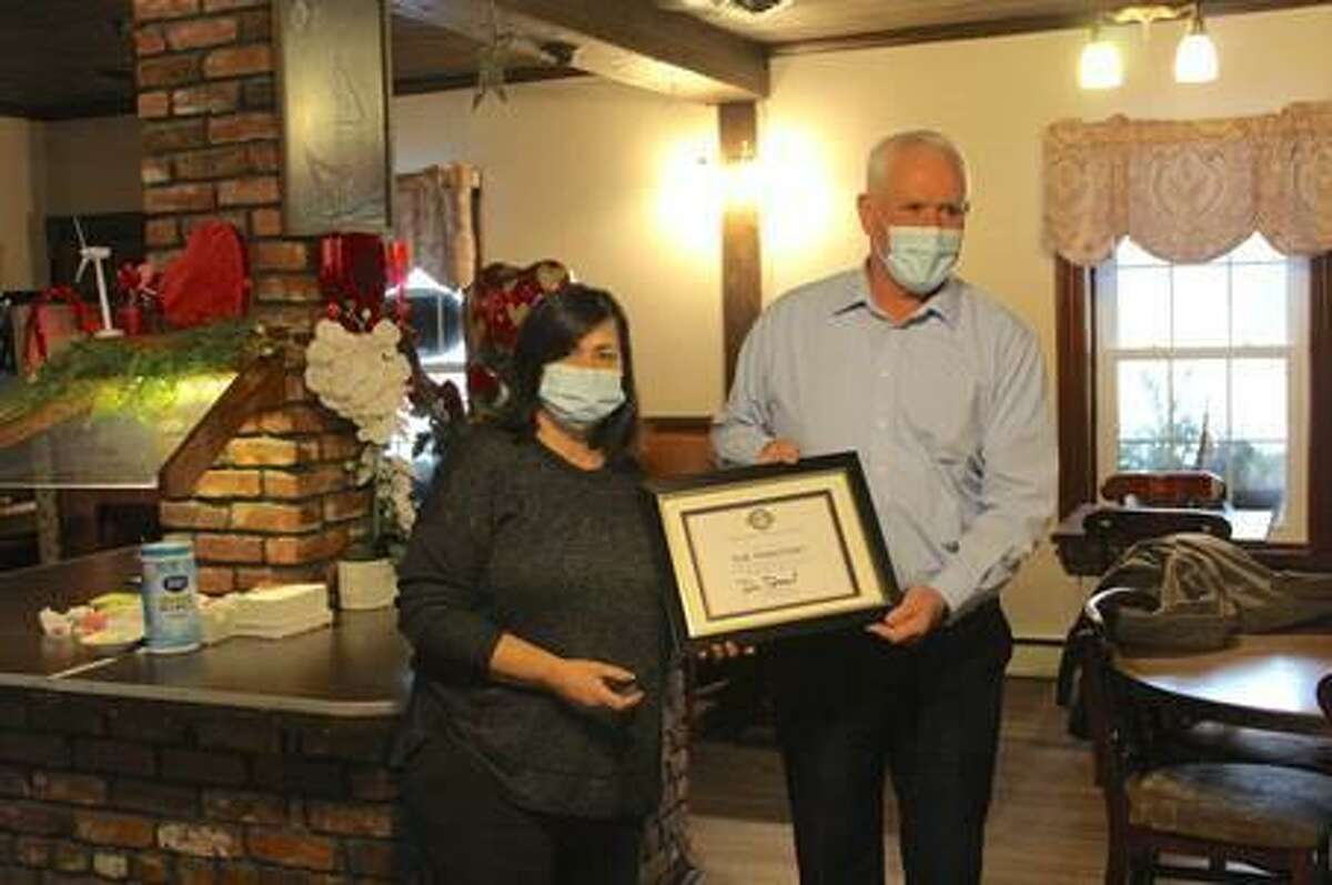 Friends of Main Street recently held a facade poster contest. From left is first place winner Voula Ignadis, The Tributary Restaurant, and Winchester Economic Development Commission chairman Dennis Dressel.