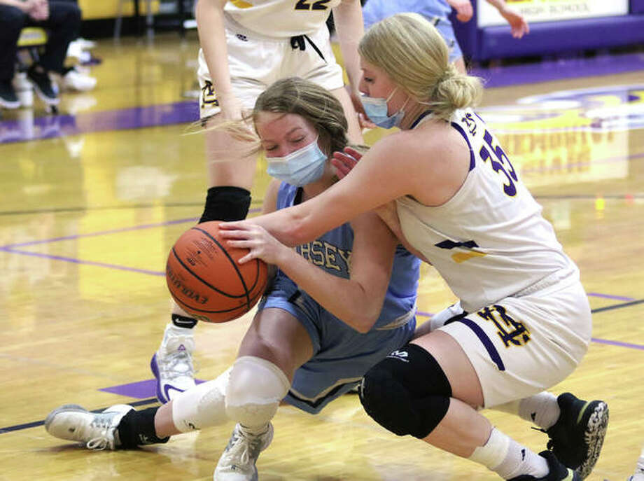 Jersey's Kari Krueger is fouled by CM's Claire Christeson (left) after securing a defensive rebound in the second half of their Mississippi Valley Conference girls basketball game Monday night in Bethalto. Photo: Greg Shashack / The Telegraph