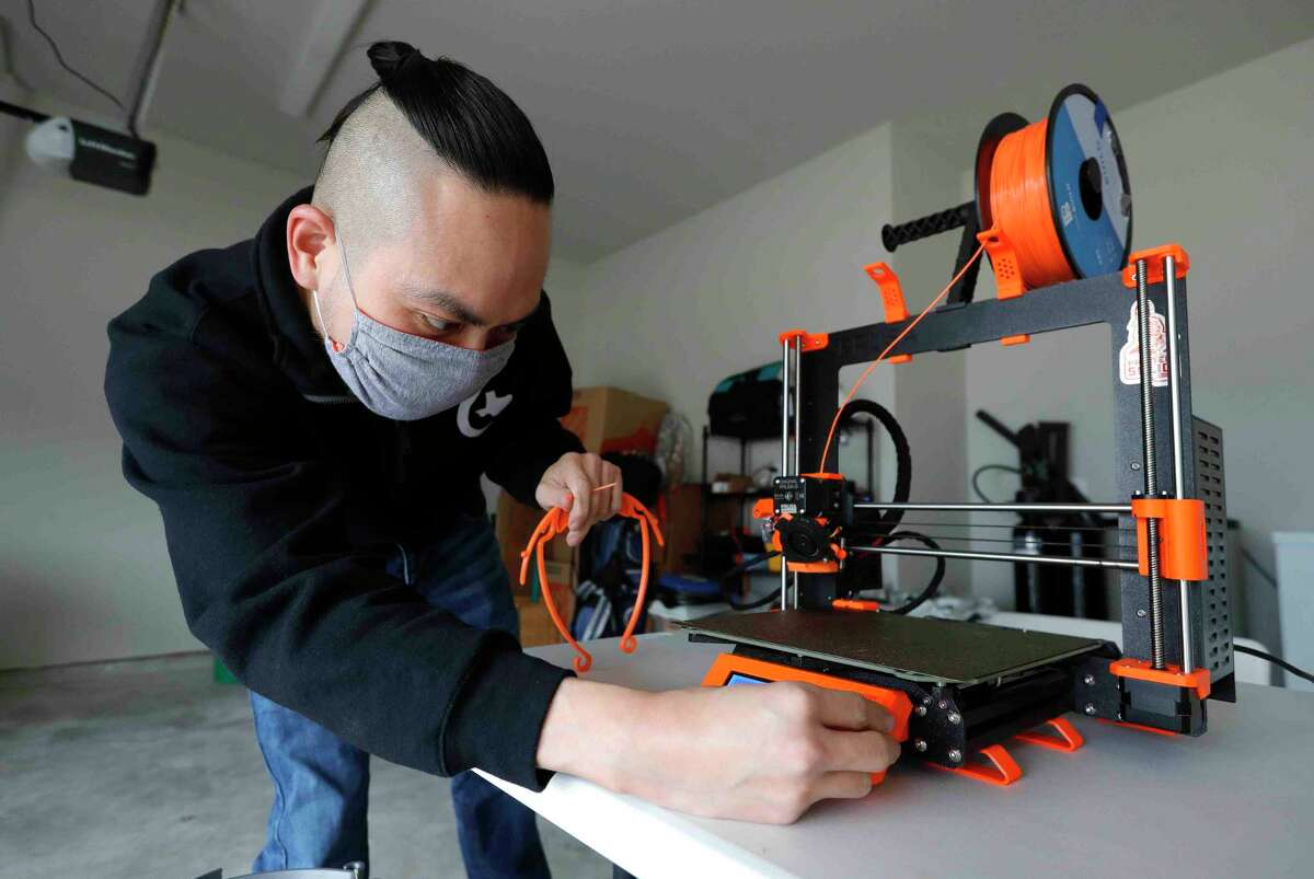 William Vo sets up a 3D printer to produce a face mask at his home, Thursday, Feb. 11, 2021, in Shenandoah. Members of College Park High School's Texas Torque robotics team have made more than 7,000 face masks for health care workers across the country.