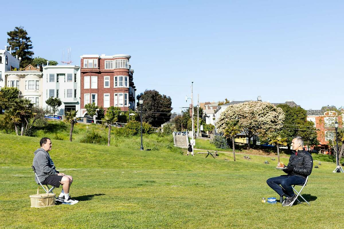Marius Greenspan (left) and Jim Maloney have breakfast while maintaining social distance at Dolores Park during the shelter-in-place order on April 1, 2020, in San Francisco.