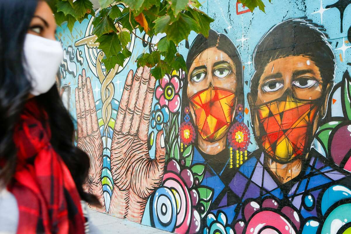 A woman walks past a Sutter Pacific Medical Foundation coronavirus mural on Valencia Street in San Francisco in October. San Francisco has not moved from the purple to red tier despite low case rates, and the reason appears to be its score on a health equity metric.
