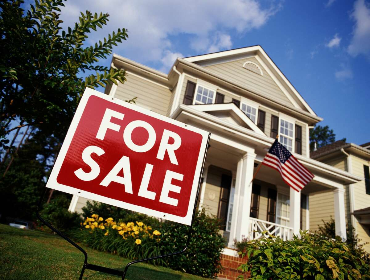 """A """"For Sale"""" sign in front of a suburban 2-story home."""