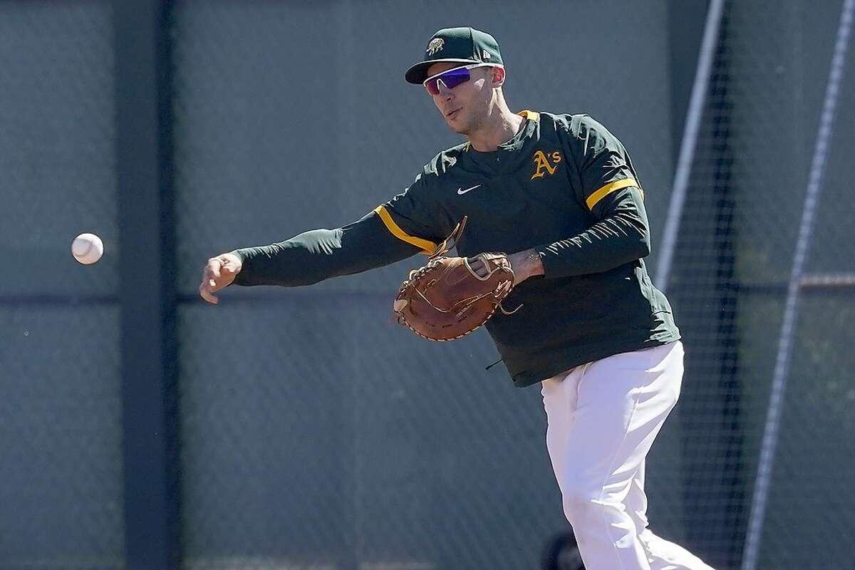 Oakland Athletics' Matt Olson throws during a spring training baseball practice, Monday, Feb. 22, 2021, in Mesa, Ariz. (AP Photo/Matt York)