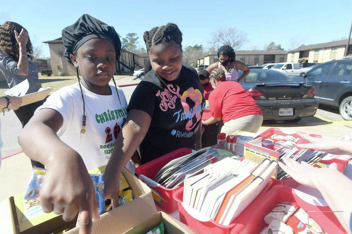 From left, Darion Johnson and Tatyana Charles select snacks after ipcking out their books during the Beaumont ISD Parent Involvement Committee's caravan Tuesday. Committee members and BISD staff joined in the event to bring books, snacks and toiletries to area students during this week's virtual learning. Photo made Tuesday, February 23, 2021 Kim Brent/The Enterprise