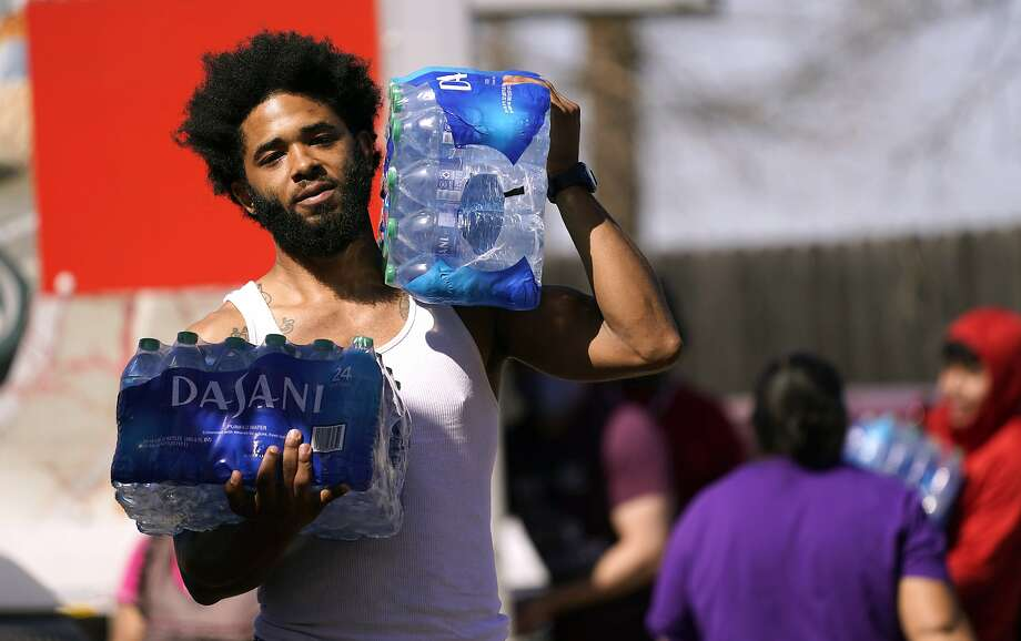 Brandon Fisher carries drinking water he was given by volunteers at an apartment complex without water Tuesday, Feb. 23, 2021, in Dallas. Two local bartenders took it upon themselves to bring a truck of drinking water to distribute to residents that have not had running water for over a week. (AP Photo/LM Otero) Photo: LM Otero, Associated Press
