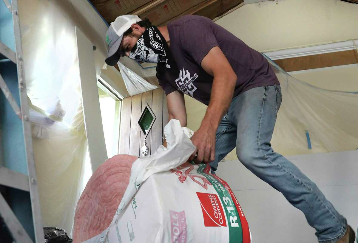 Adam and Patricia Baugh are in the process of woking on parts of their house and front yard landscaping, on Tuesday, April 21, 2020. Adam opens a roll of insulation to be stapled to the ceiling before the sheet rock goes in.