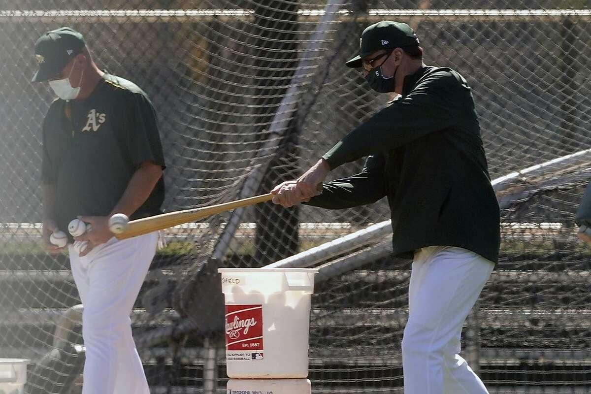 Oakland Athletics manager Bob Melvin, right, hits a ball during a spring training baseball practice, Monday, Feb. 22, 2021, in Mesa, Ariz. (AP Photo/Matt York)