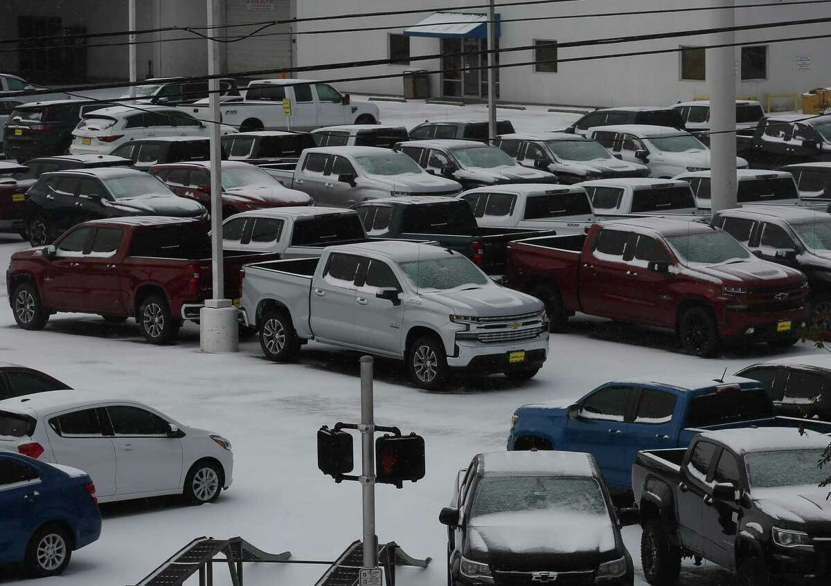 Snow-covered vehicles are sitting at a dealership lot on Katy Freeway Monday, Feb. 15, 2021, in Houston.
