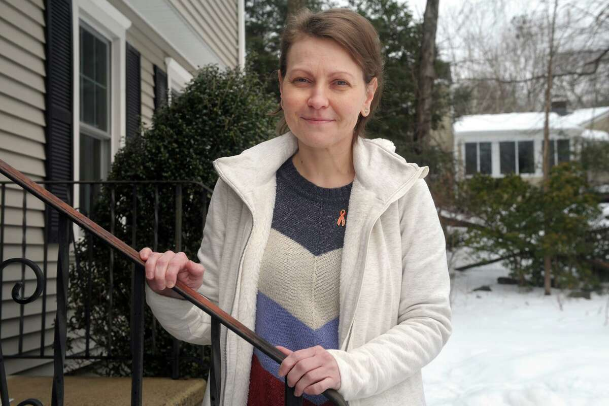 Christina Lee poses in front of her home in Trumbull, Conn. Feb. 23, 2021. Lee, who is being treated for leukemia, is seeking guidance after hearing the state has deprioritized COVID-19 vaccinations for some people with pre-existing conditions.
