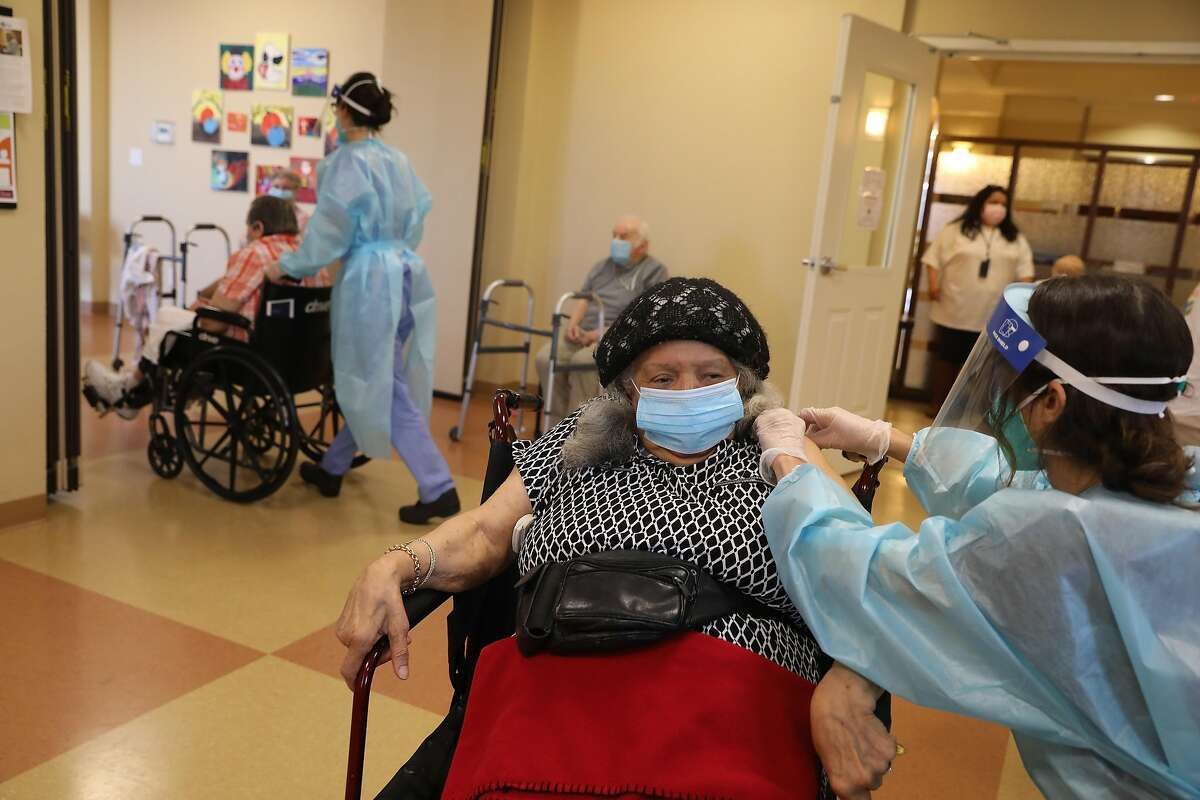 Casey Domine (right), CVS nurse, gives the Pfizer COVID-19 vaccine to Norma Paglinawan (left), 93, at the Peninsula Del Rey vaccine clinic where COVID-19 vaccines were administered in the senior community Friday January 15th.  2021 in Daly City, California.  CVS administered the vaccine clinic.