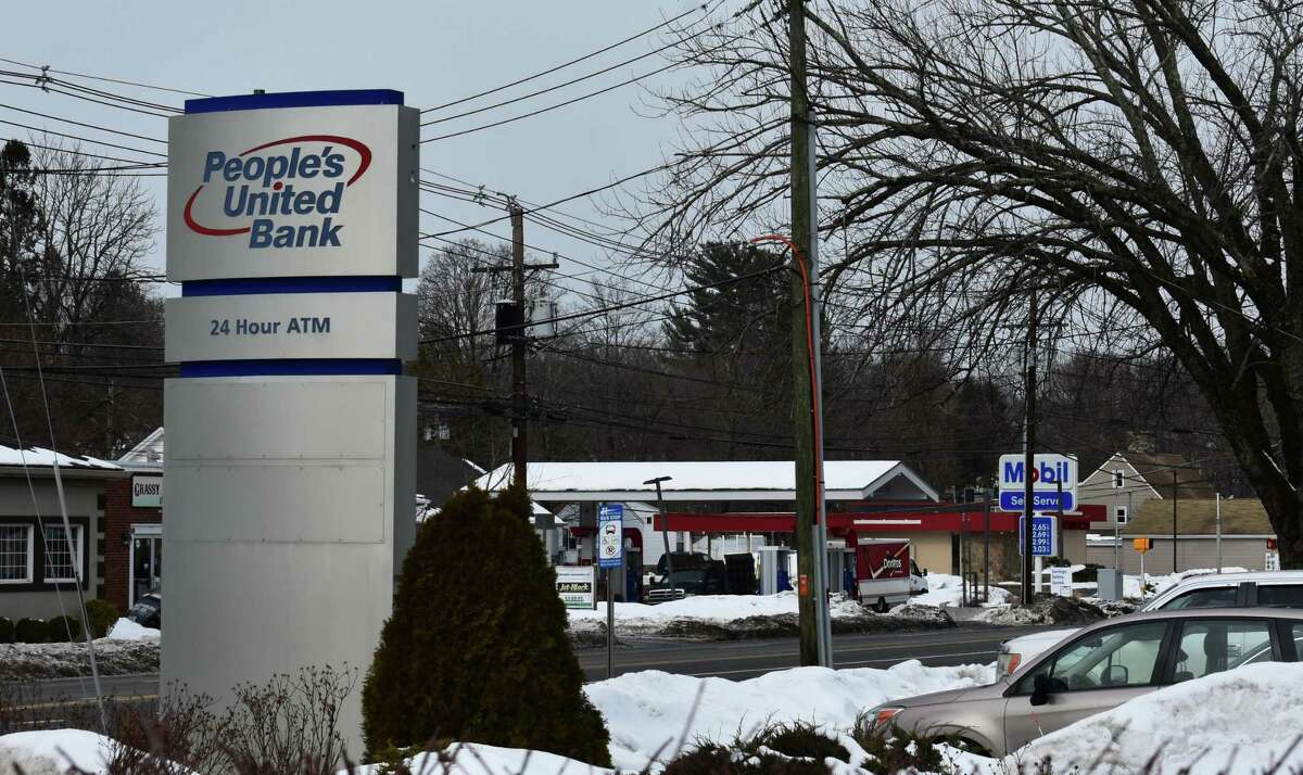 The People's United Bank logo in Bethel, Conn., with the town's shuttered Bank of America branch in the background behind a gas station. With People's United trailing only Bank of America for Connecticut deposits in 2020, M&T will phase out the brand in favor of its own as an outcome of its proposed $7.6 billion acquisition of People's United.