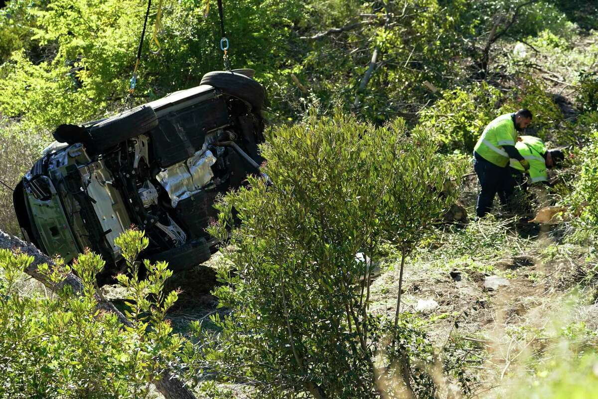 Workers remove debris near a vehicle on its side after a rollover accident involving golfer Tiger Woods Tuesday, Feb. 23, 2021, in Rancho Palos Verdes, Calif., a suburb of Los Angeles. Woods suffered leg injuries in the one-car accident and was undergoing surgery, authorities and his manager said.