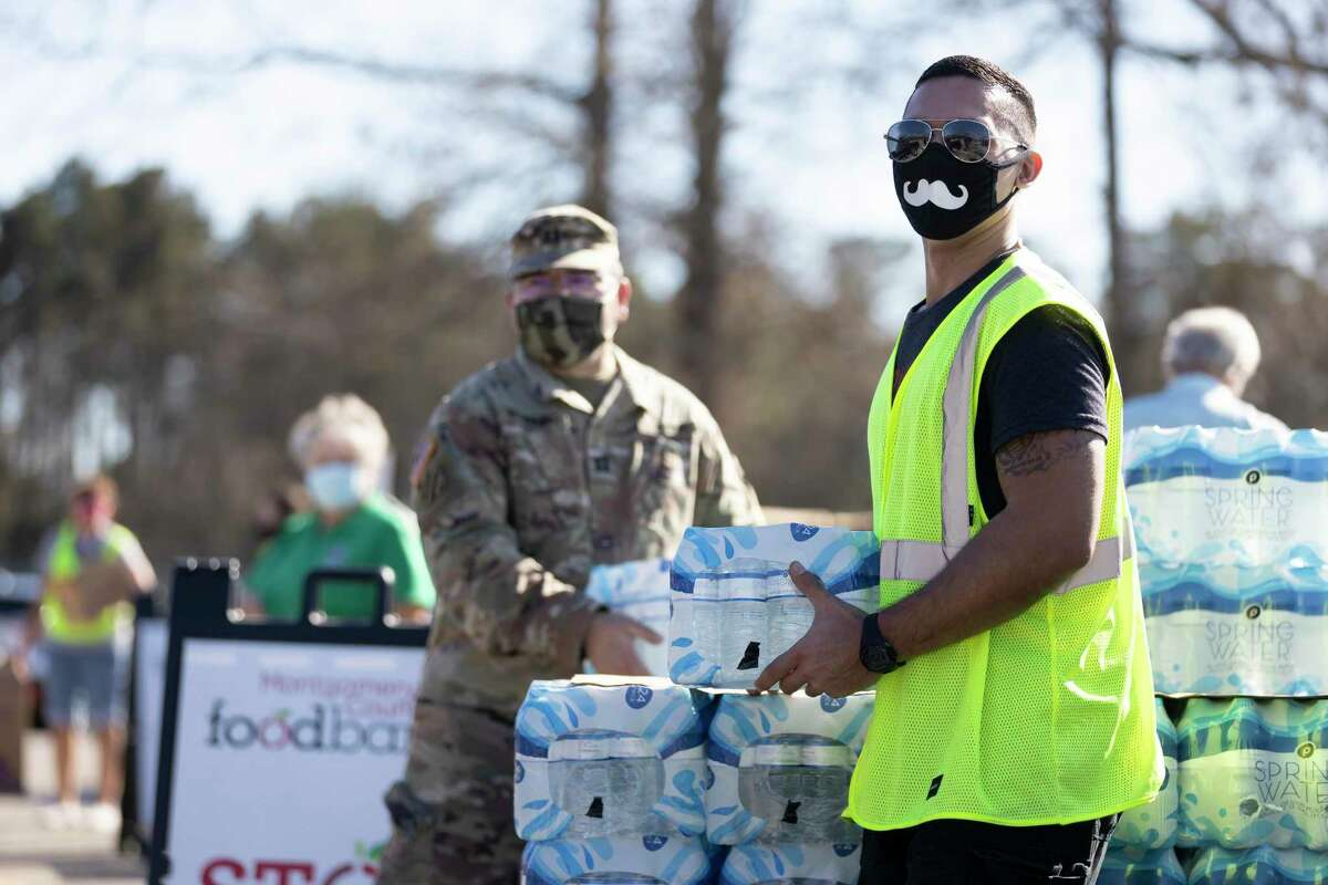 Ben Lacount with the Montgomery County Medical Reserve Corps prepares to load water during a water distribution event hosted by the Montgomery County Food Bank, Tuesday, Feb. 23, 2021, held at Bull Sallas Park in New Caney. The food bank increased the amount of supplies they brought to the event from 400 to 500 in anticipation of greater need in the community.