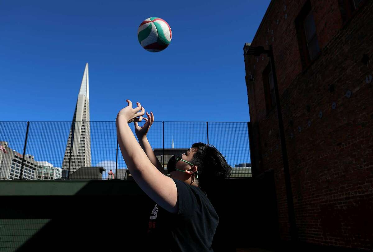 "Galileo High senior Daniel Feliciano hits a volleyball Saturday at the newly renovated Willie ""Woo Woo"" Wong Playground."