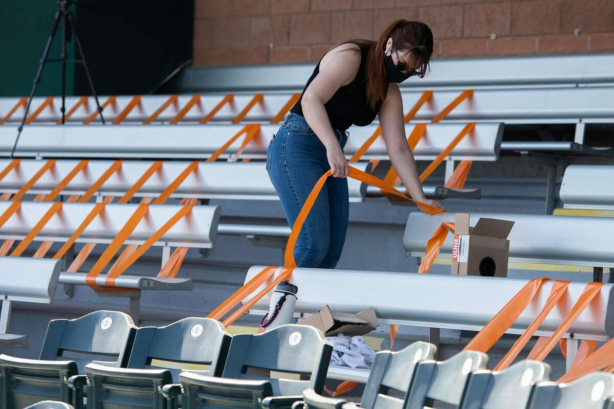 Jacquie Freeman, Spring Training Operations Assistant blocks off seats in which people can't sit to enforce social distancing before opening day of spring training in the Cactus League at Scottsdale Stadium on Tuesday, Feb. 23, 2021, in Scottsdale, Ariz.