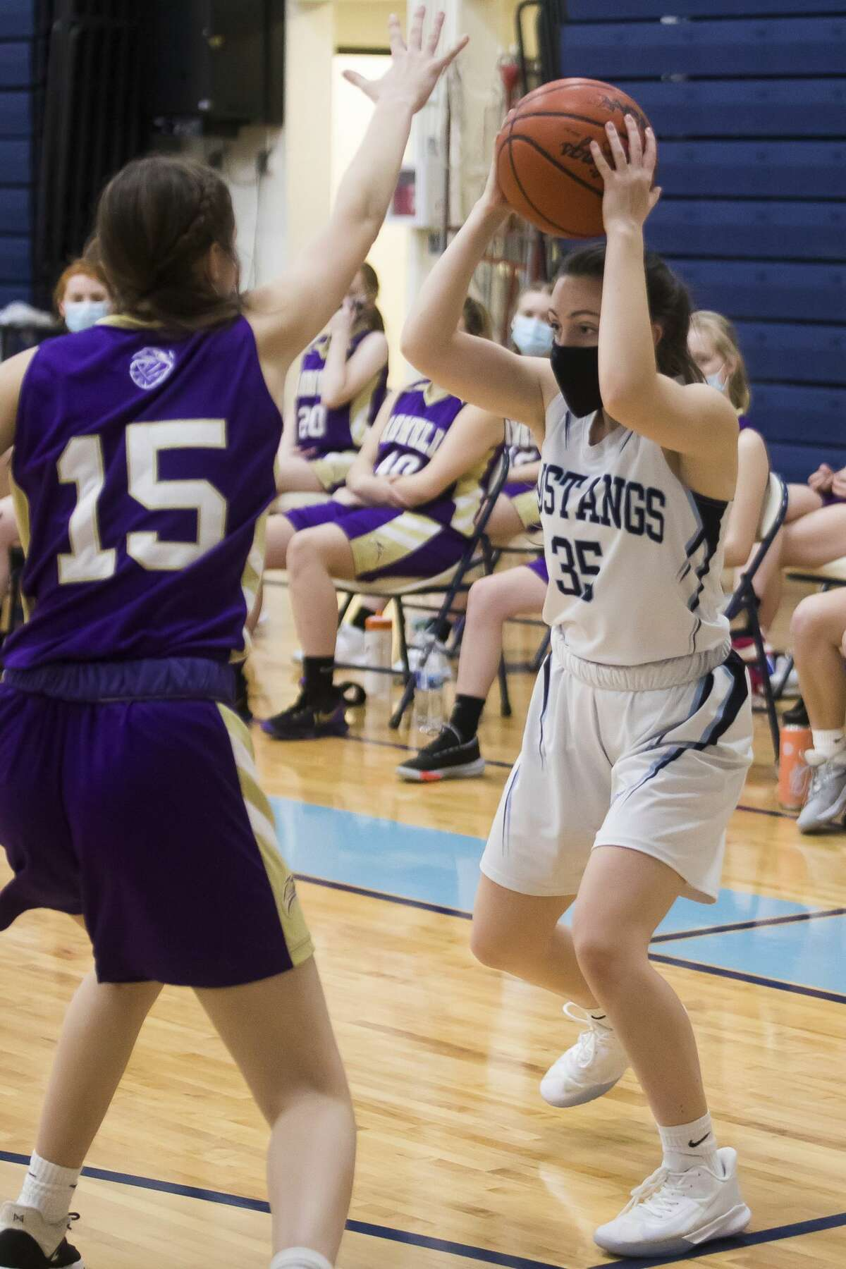 Meridian's Trinity Kolka looks for a teammate to pass to during the Mustangs' game against Farwell Tuesday, Feb. 23, 2021 at Meridian Early College High School. (Katy Kildee/kkildee@mdn.net)