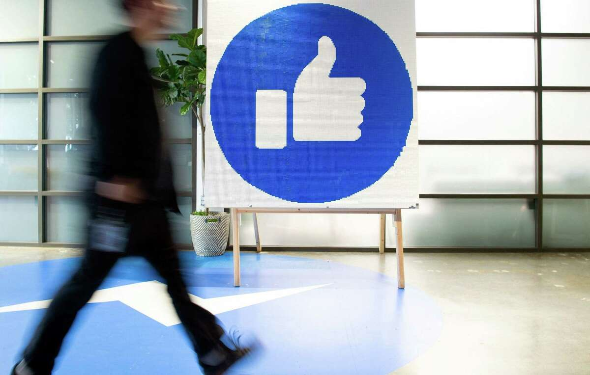 This file photo taken on October 23, 2019 shows a Facebook employee walking past a sign displaying the