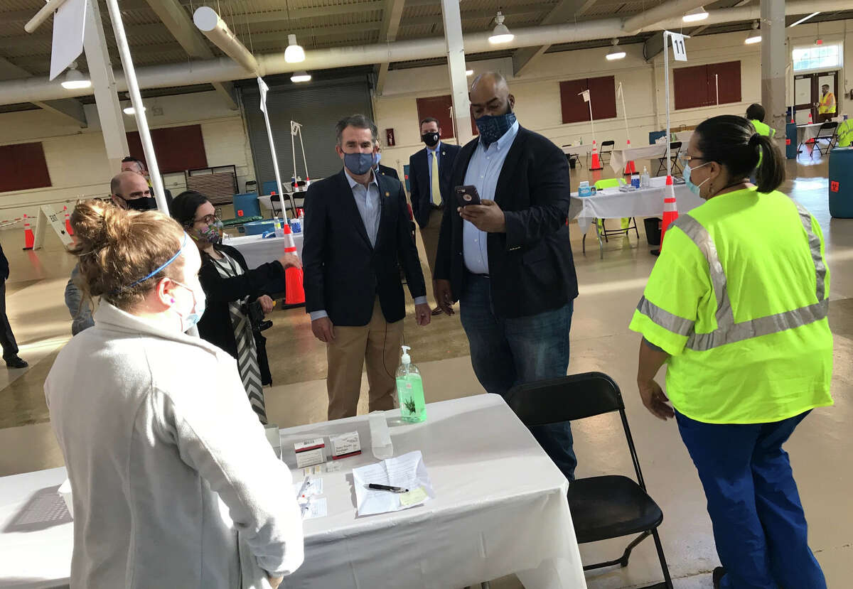Virginia Gov. Ralph Northam and Del. Lamont Bagby, D-Henrico, talk with nurses at a mass vaccination event last month in Henrico County.
