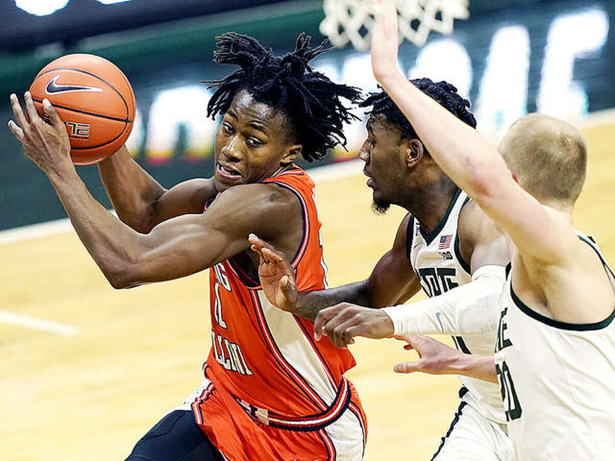 Illinois guard Ayo Dosunmu (11) drives as Michigan State guard A.J. Hoggard, center, and forward Joey Hauser defend Tuesday night in East Lansing, Mich.