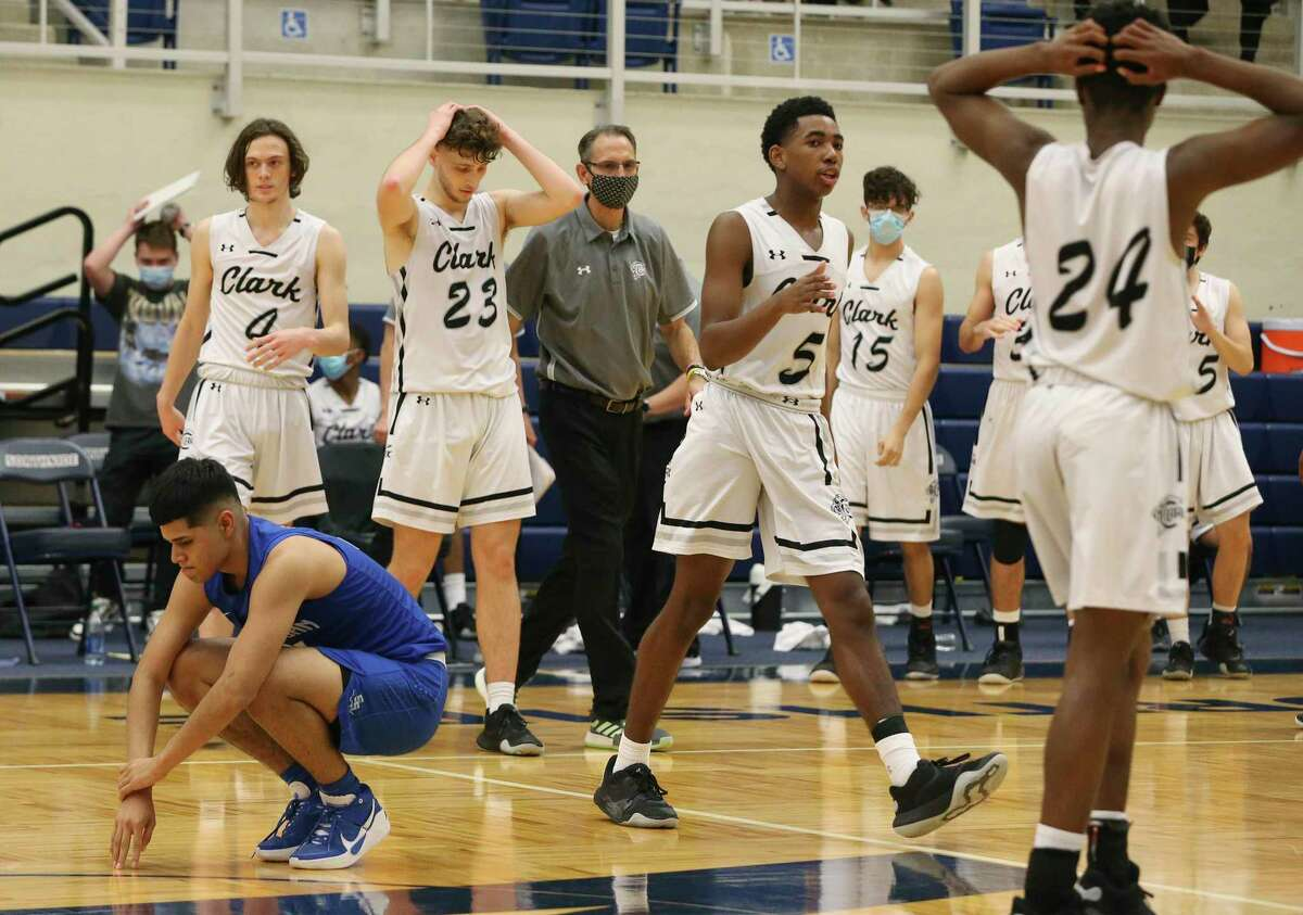 Clark players show a sense of relief as South San's Josue Rivera (kneeling) expresses his grief after the Bobcats missed a game-winning shot in the UIL Class 6A first round playoff basketball game at Paul Taylor Fieldhouse on Tuesday, Feb. 23, 2021. Clark defeated South San, 32-31, to move on in the playoffs.