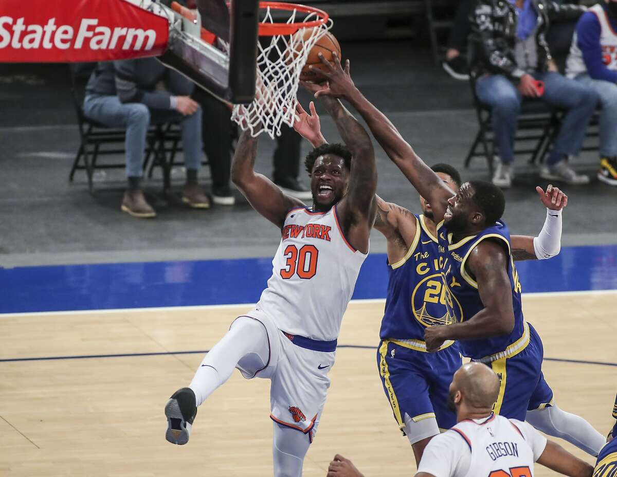 New York Knicks forward Julius Randle (30) moves to the basket as Golden State Warriors, including Draymond Green (23), defend during the third quarter of an NBA basketball game Tuesday, Feb. 23, 2021, in New York. (Wendell Cruz/Pool Photo via AP)