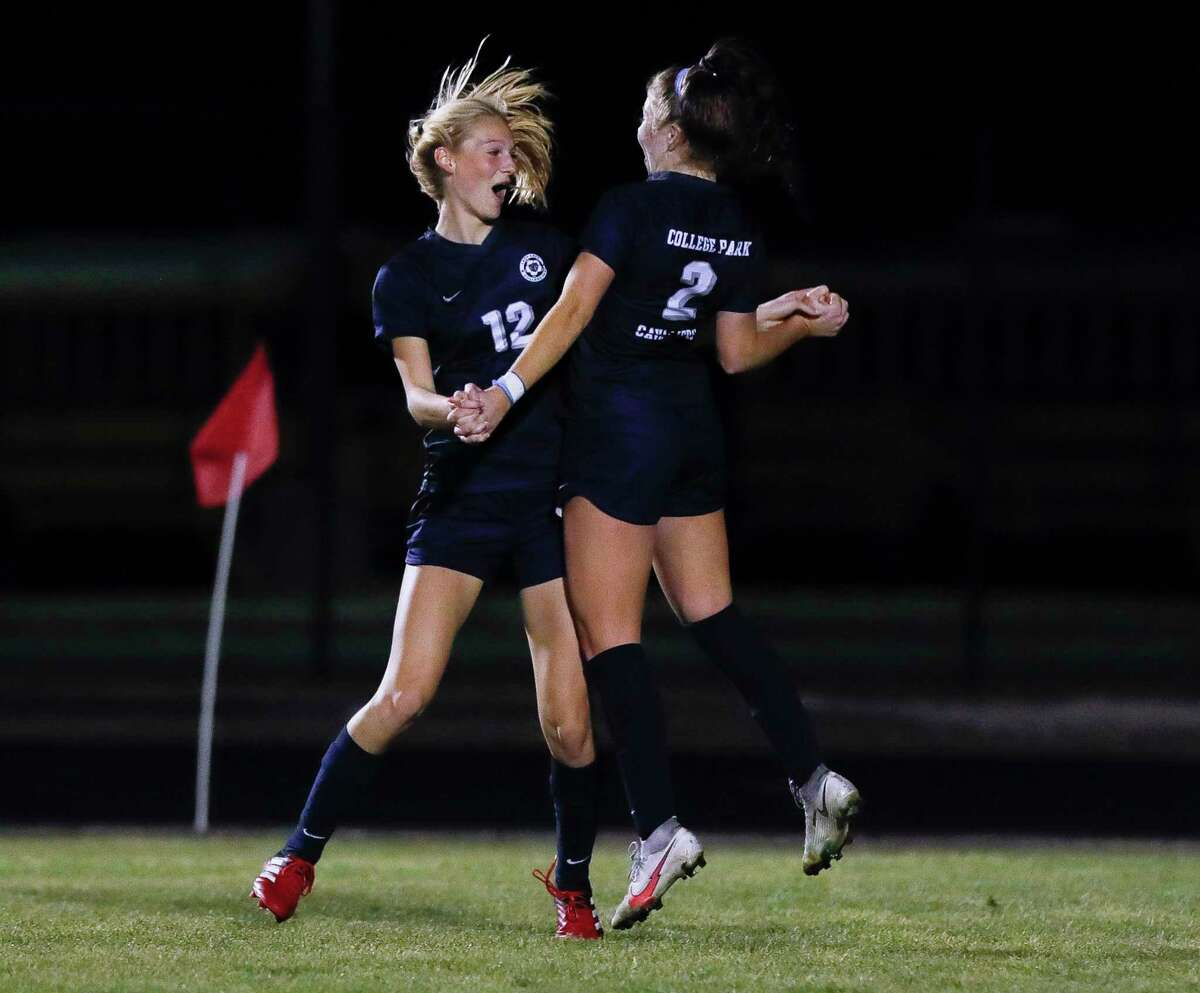 College Park's Carli Rabson (12) reacts with Ashely Washburn (2) after scoring a goal during the first period of a District 13-6A high school soccer match at College Park High School, Tuesday, Feb. 23, 2021, in The Woodlands.