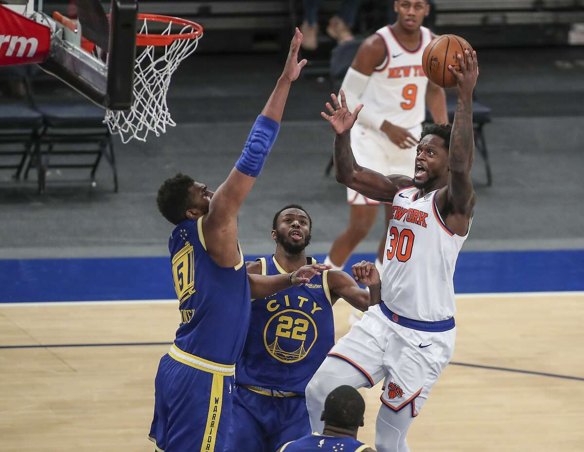 Knicks forward Julius Randle shoots against Warriors' Kevon Looney (5) and Andrew Wiggins in the third. Wiggins had 25 points, 10 rebounds and 7 assists.