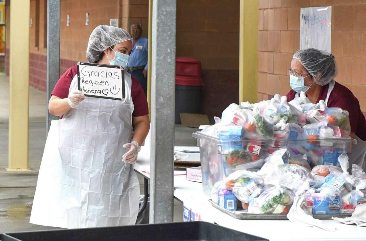 La trabajadora de la cafetería Sonia C. Herrera reparte paquetes de desayuno y almuerzo a los estudiantes, el 23 de marzo de 2020, durante el programa de comidas LISD Grab and Go en J.Z. Escuela Primaria Leyendecker.